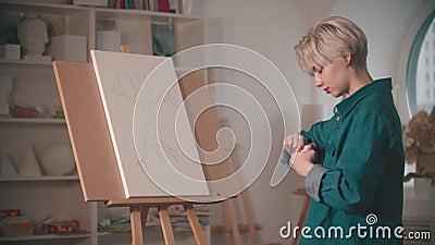 Una giovane artista apre una pittura beige per colorare il suo dipinto stock footage