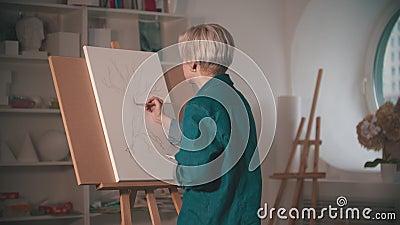 Una giovane artista comincia a dipingere il suo schizzo a colori beige nello studio d'arte stock footage