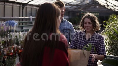 Una giovane coppia di europei riceve cibo biologico in sacchetto di carta marrone da una donna venditrice in serra Un uomo che pa stock footage