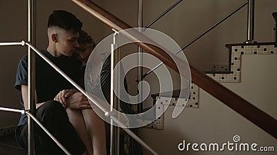 Una giovane coppia felice e amorevole parla e sorride seduta per le scale nel salotto di casa. archivi video