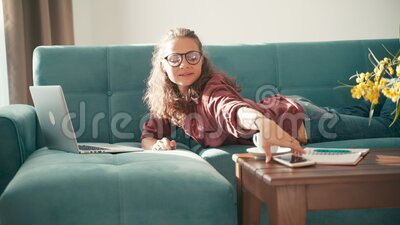 Una giovane donna allegra che lavora da casa, sdraiata su un divano con un portatile video d archivio