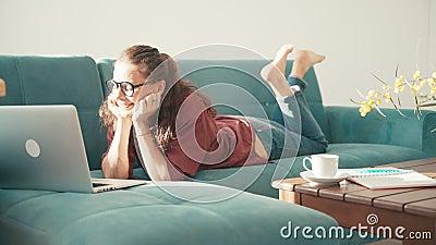 Una giovane donna allegra sdraiata su un divano blu in un soggiorno con un portatile archivi video