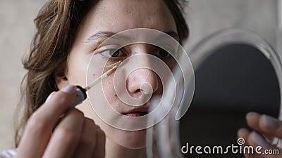 Una giovane donna applica un diffusore con una spazzola sotto l'occhio e guarda in un piccolo specchio Configurazione di base stock footage