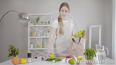 Una giovane donna caucasica sicura porta frutta e verdura dalla borsa a casa Una ragazza molto magra che cucina in modo salutare archivi video