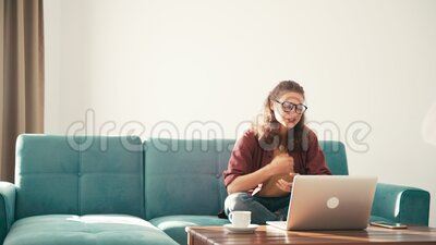 Una giovane donna che beve caffè con gli occhiali mentre fa una videochiamata con gli amici video d archivio