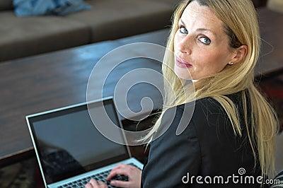 Una giovane donna di affari che usando una cima del rivestimento
