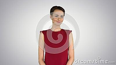 Una giovane donna elegante è d'accordo con qualcuno e sorride alla telecamera su sfondo sfumato stock footage