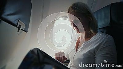 Una giovane donna sta leggendo una rivista nella cabina di pilotaggio di un aeroplano Comodità e spettacolo nel viaggio archivi video