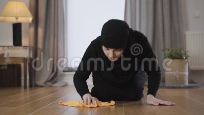 Una giovane musulmana in hijab pulisce il pavimento con uno straccio giallo Una casalinga orientale che soffia al suolo video d archivio