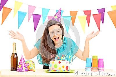 Una hembra del feliz cumpleaños con un sombrero del partido que gesticula con su mano