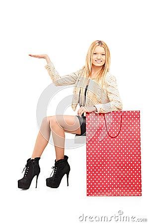 Una hembra joven atractiva que gesticula al lado de un bolso de compras
