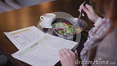 Una joven atractiva lleva un estilo de vida sano, se adhiere a una nutrición adecuada y comprueba el contenido calórico de los pr metrajes