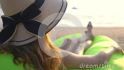 Una joven con un sombrero de paja que disfruta de paz y privacidad al atardecer en la playa almacen de video