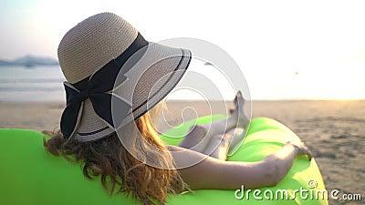 Una joven con un sombrero de paja que disfruta de paz y privacidad al atardecer en la playa almacen de metraje de vídeo