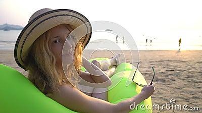 Una joven con un sombrero de paja que disfruta de paz y privacidad al atardecer en la playa metrajes