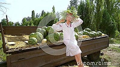 Una modelo feliz posando con trajes folclóricos cerca de las sandías recolectadas almacen de video