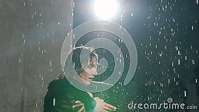 Una muchacha caucásica joven realiza una danza moderna descalzo en el agua bajo gotas de lluvia en el estudio Danza emocional metrajes