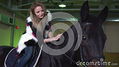 Una muchacha del caballo y frotar ligeramente su mano mientras que la situación del caballo indoor almacen de video