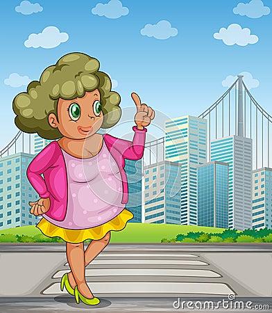 Una muchacha gorda en la calle a través de los edificios altos