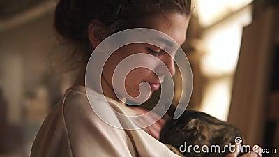 Una muchacha joven, hermosa está jugando con un gato apacible, gris Él que rasguña sus oídos, caricias Feliz indoor almacen de metraje de vídeo