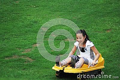 Una muchacha que hace el movimiento resbaladizo de la hierba