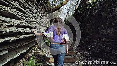 Una muchacha sube las escaleras de piedra en la grieta de la montaña y explora la formación de roca metrajes