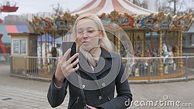 Una mujer caminando por un parque de atracciones desierto, hablando en video chat An Influencer hace la transmisión del smartphon almacen de video