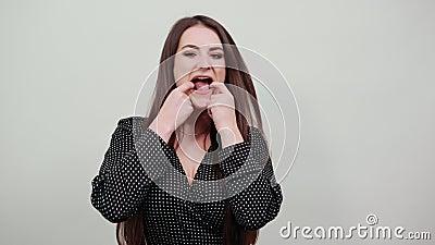 Una mujer caucásica encantadora estira la boca con los dedos almacen de video