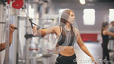 Una mujer del atleta que camina en el gimnasio y que pone en los auriculares - consiga sus manos en las manijas y comience el ent almacen de metraje de vídeo