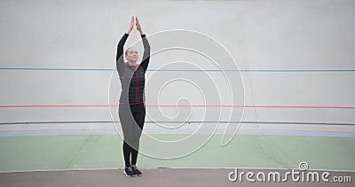 Una mujer deportista delgada que practica yoga fitness en el exterior, con un fondo blanco metrajes