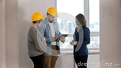 Una mujer embarazada con su marido firmando papeles para el alquiler del apartamento con un agente inmobiliario almacen de video