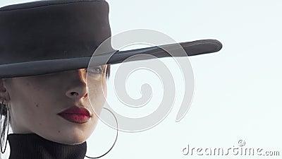 Una mujer grandiosa de labios rojos con un sombrero negro mirando hacia otro lado con cuidado almacen de metraje de vídeo