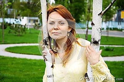Una mujer joven cerca del árbol