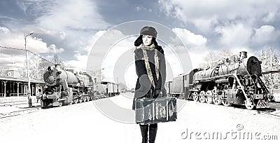 Una mujer joven delante de un ferrocarril viejo