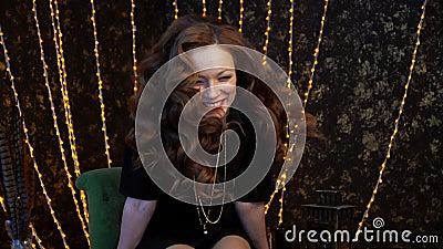 Una mujer joven en el vestido oscuro que se sienta en una butaca del vintage con el pelo flojo almacen de video