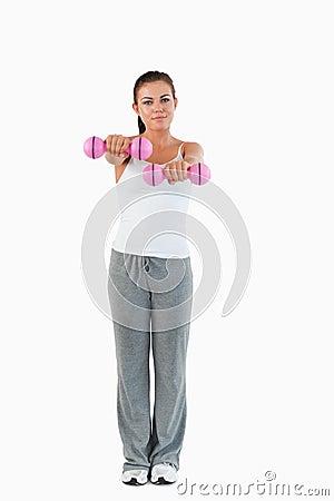 Una mujer linda que se resuelve con pesas de gimnasia
