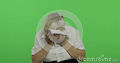 Una mujer mayor estornuda Enfriado Vieja abuela Llave de la croma metrajes
