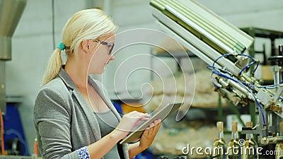 Una mujer trabaja con una tableta en el lagar Un transportador con las botellas de vino está corriendo alrededor de él Industria  almacen de video