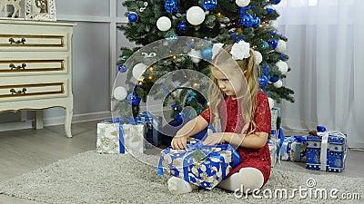Una niña en un vestido azul desempaqueta un regalo del ` s del Año Nuevo debajo de un árbol de navidad metrajes