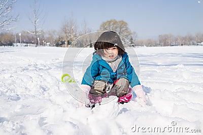 Muchacha que juega feliz en la nieve