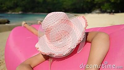Una niña pequeña con un sombrero de paja rosa tendido en un sofá inflable en una playa almacen de video