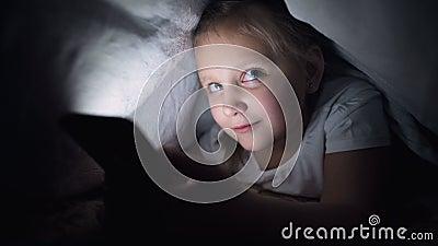 Una niña pequeña se esconde bajo una manta para usar un dispositivo digital para smartphones después de dormir Soledad de almacen de video