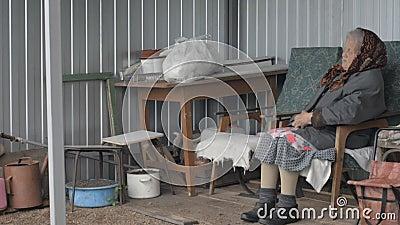 Una nonna anziana che si siede in una sedia sulla via archivi video