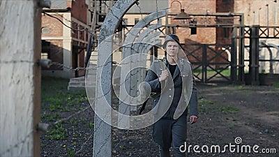 Una opinión cercana un actor de sexo masculino joven se vistió como soldado alemán cerca de una cerca del alambre de púas que gua almacen de metraje de vídeo
