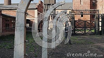 Una opinión cercana un actor de sexo masculino joven vestido como soldado alemán cerca de una cerca del alambre de púas que guard metrajes