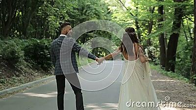 Una pareja casada hermosa que camina abajo del parque y que lleva a cabo sus manos Alineada de boda Árboles verdes en el fondo almacen de video