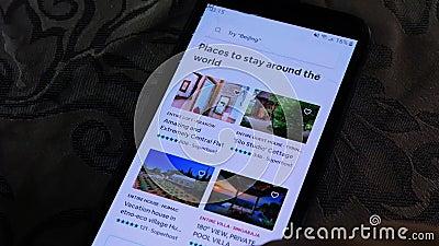 Una persona che usa l'app Airbnb su uno smartphone - esplorando le destinazioni di viaggio archivi video