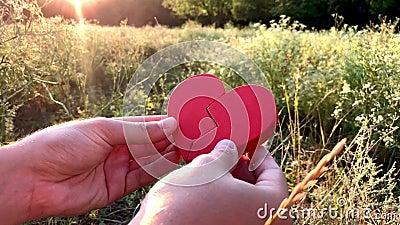 Una persona stacca e si unisce due metà di cuore rosso Pensando all'amore ed alle relazioni psicologia Timore di perdita video d archivio