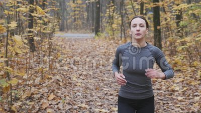 Una portatrice di abbigliamento sportivo nero e grigio che corre nel parco Donna motivata che corre nella foresta archivi video