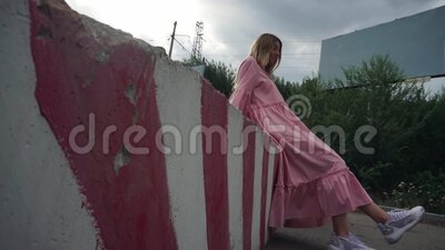 Una ragazza in abito rosa siede su un blocco di calcestruzzo, un cartellone vuoto sullo sfondo video d archivio